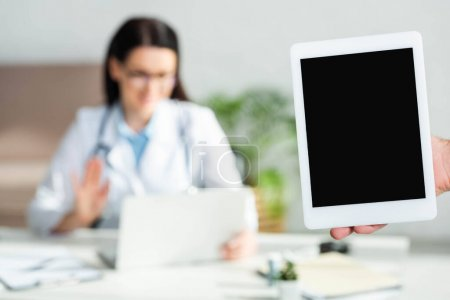 Photo for Cropped view of man holding digital tablet with blank screen in clinic office with doctor having online consultation on laptop, selective focus - Royalty Free Image