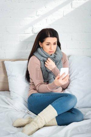 Photo pour Une femme malade qui consulte un médecin en ligne au moyen d'un téléphone intelligent - image libre de droit