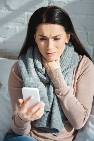 Photo for Sick woman having online consultation with doctor on smartphone - Royalty Free Image