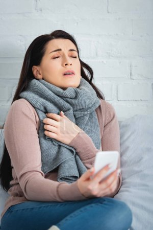 tired ill woman having online consultation with doctor on smartphone