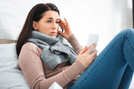 Photo pour Une femme fatiguée souffrant de maux de tête une consultation en ligne avec un médecin au moyen d'un téléphone intelligent - image libre de droit