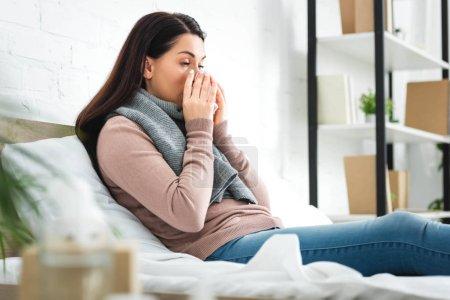 Photo pour Femme malade en écharpe avec nez qui coule tenant la serviette à la maison - image libre de droit