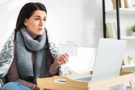 Photo for Cold woman with thermometer having online consultation with doctor on laptop - Royalty Free Image