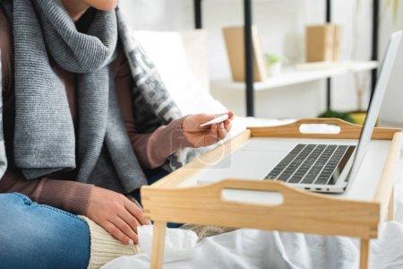 Photo pour Crochet vue d'une femme malade avec fièvre consultation en ligne avec un médecin sur un ordinateur portatif - image libre de droit