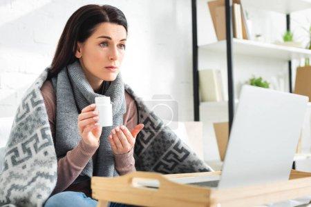 Photo pour Une femme malade tient des pilules et consulte un médecin en ligne sur un ordinateur portable - image libre de droit