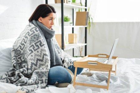 Photo pour Une femme malade consulte un médecin en ligne sur un ordinateur portatif - image libre de droit