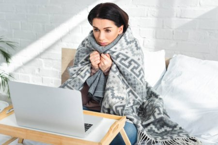 attractive ill woman having online consultation with doctor on laptop at home