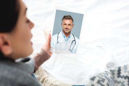 Photo pour Une femme malade qui consulte en ligne un médecin de sexe masculin sur un comprimé numérique - image libre de droit