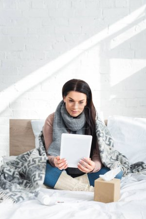 Photo pour Une femme malade souffrant de grippe une consultation en ligne avec un médecin sur un comprimé numérique - image libre de droit