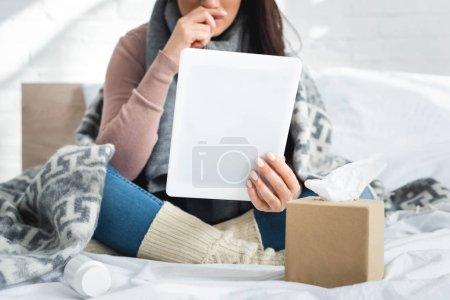 Photo pour Vue recadrée de femme malade bouleversée avec la grippe ayant consultation en ligne avec le médecin sur tablette numérique - image libre de droit