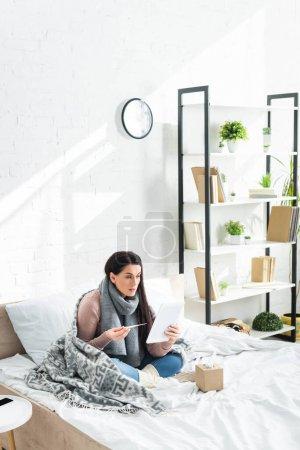 Photo pour Une femme malade attrayante avec fièvre une consultation en ligne avec un médecin sur un comprimé numérique - image libre de droit