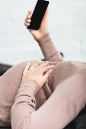 Photo pour Vue en coupe d'une femme enceinte ayant une consultation en ligne avec un médecin sur smartphone - image libre de droit