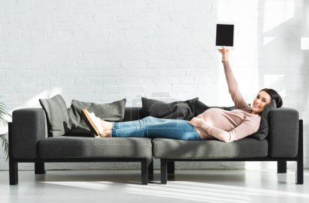 Photo for Smiling pregnant woman holding digital tablet with blank screen while lying on sofa - Royalty Free Image