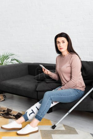 Photo for Woman with broken leg and crutches having online consultation with doctor on smartphone on sofa - Royalty Free Image