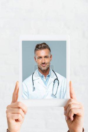 Photo pour Vue recadrée de la femme tenant tablette numérique avec un médecin sur la consultation en ligne, sur blanc - image libre de droit