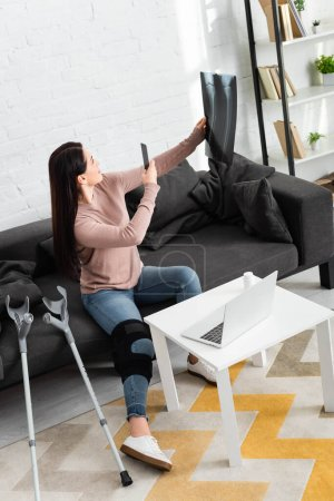 Photo pour Femme prenant une photo de la jambe radiographie pour consultation en ligne avec le médecin sur ordinateur portable - image libre de droit
