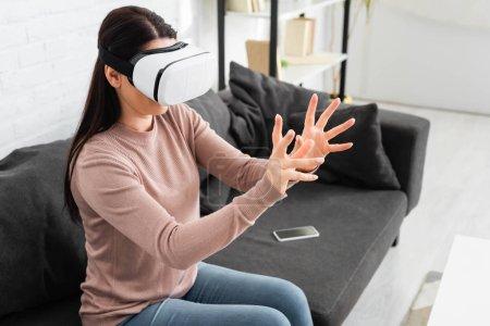 """Photo pour Femme émotionnelle utilisant un casque d """"écoute de réalité virtuelle assise sur un canapé avec un téléphone intelligent - image libre de droit"""