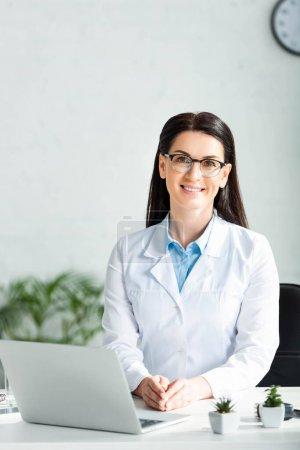 Photo pour Une femme médecin souriante assise dans un bureau de clinique avec un ordinateur portatif - image libre de droit