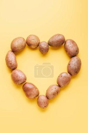 Photo pour Vue du dessus des pommes de terre crues fraîches entières disposées en coeur sur fond jaune - image libre de droit