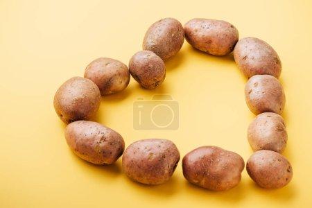 Photo pour Pommes de terre crues fraîches entières disposées en coeur sur fond jaune - image libre de droit