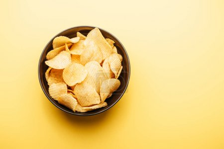 Photo for Top view of delicious crispy potato chips in bowl on yellow background - Royalty Free Image