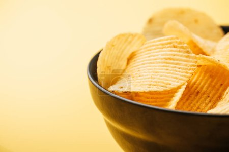 Photo for Close up view of delicious crispy potato chips in bowl on yellow background - Royalty Free Image