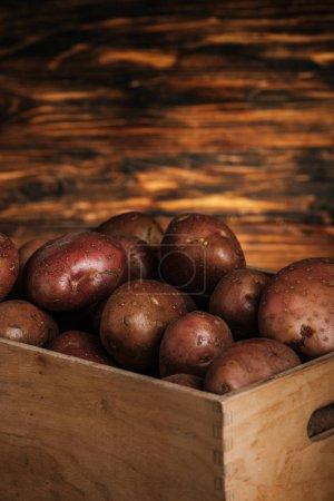 Photo pour Vue de près des pommes de terre fraîches mûres dans une boîte sur fond de bois - image libre de droit