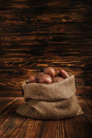 Photo pour Pommes de terre mûres en sac rustique sur fond de bois - image libre de droit
