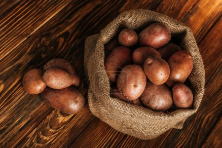 top view of ripe potatoes in rustic sack on wooden background
