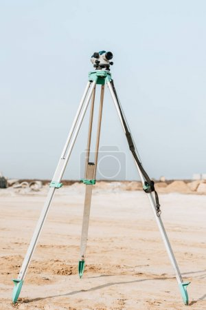Photo for Digital level for geodesic measuring on dirt road with blue sky at background - Royalty Free Image