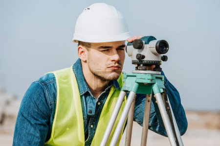 Photo for Surveyor in hardhat and high visibility jacket using digital level - Royalty Free Image