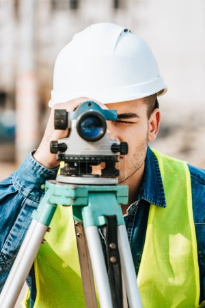 Photo for Surveyor in hardhat and high visibility jacket looking throughout digital level - Royalty Free Image
