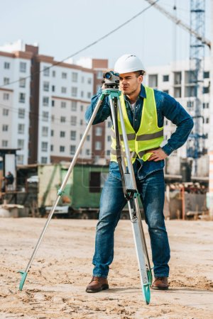 Photo for Surveyor in hardhat and high visibility jacket using digital level on construction site - Royalty Free Image