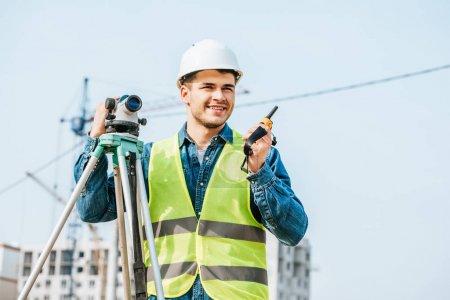 Photo pour Sondeur souriant au niveau numérique parlant à la radio avec le chantier à l'arrière-plan - image libre de droit