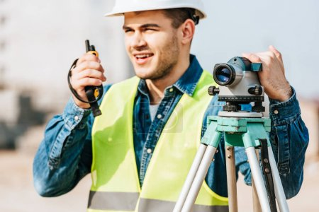 Photo for Selective focus of surveyor holding digital level and talking on radio set - Royalty Free Image