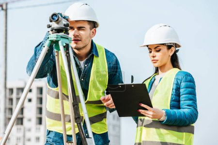 Photo for Surveyor using digital level while colleague writing on clipboard - Royalty Free Image