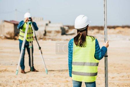 Photo pour Concentration sélective de la règle de maintien de l'arpenteur et de son collègue au niveau numérique sur le fond - image libre de droit