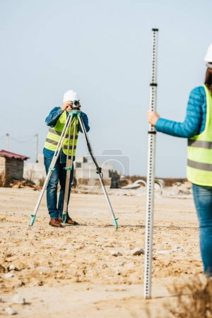 Photo for Selective focus of surveyors working with ruler and digital level on construction site - Royalty Free Image