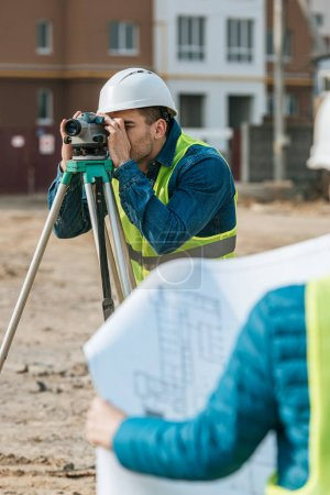 Photo for Selective focus of surveyors working with digital level and blueprint - Royalty Free Image