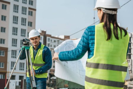Selective focus of surveyor with digital level and colleague with blueprint