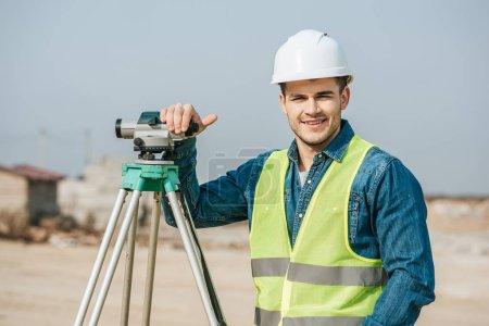 Photo pour Sondeur souriant avec niveau numérique regardant la caméra - image libre de droit
