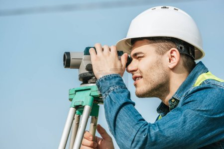 Photo for Side view of surveyor in hardhat looking throughout digital level - Royalty Free Image