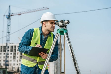 Photo for Surveyor looking throughout digital level and writing on clipboard - Royalty Free Image