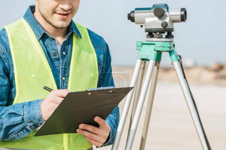 Photo pour Plan recadré d'un arpenteur souriant écrivant sur un presse-papiers à côté du niveau numérique - image libre de droit