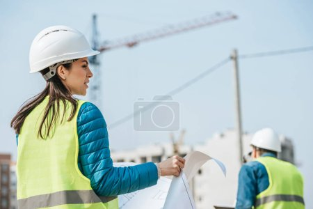 Selective focus of surveyors with blueprint on construction site