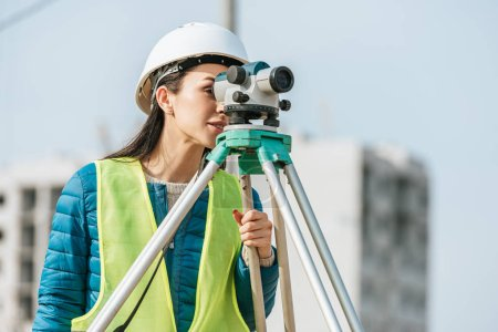 Photo for Surveyor in hardhat and high visibility jacket looking in digital level - Royalty Free Image