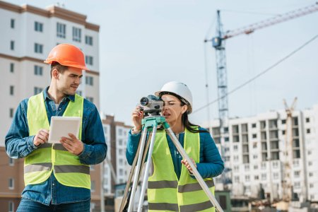Photo for Surveyors working with digital tablet and measuring level on construction site - Royalty Free Image
