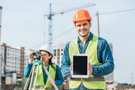 Photo for Smiling surveyor holding digital tablet with blank screen and colleague with measuring level at background - Royalty Free Image