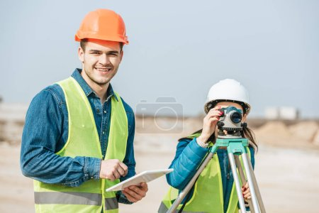 Photo for Smiling surveyor with digital tablet and colleague with measuring level - Royalty Free Image