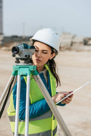 Photo for Surveyor with digital tablet looking through measuring level - Royalty Free Image